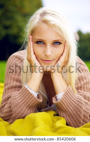 Beautiful girl lying in a park - stock photo