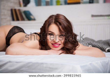 beautiful girl lying in bed in the morning in underwear and smiling - stock photo