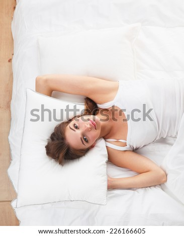 Beautiful girl lying in bedroom at early morning , isolated