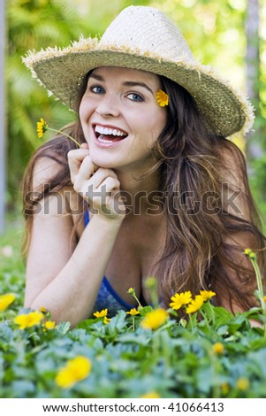 Beautiful girl lying in grass smiling with yellow flowers wearing a hat - stock photo