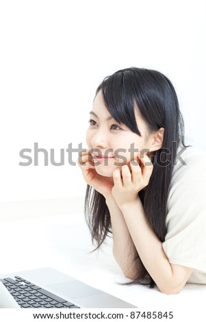 beautiful girl lying on bed with laptop - stock photo