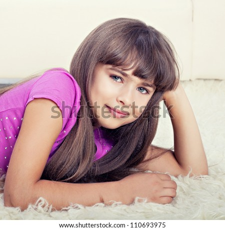 Beautiful girl lying on floor - stock photo