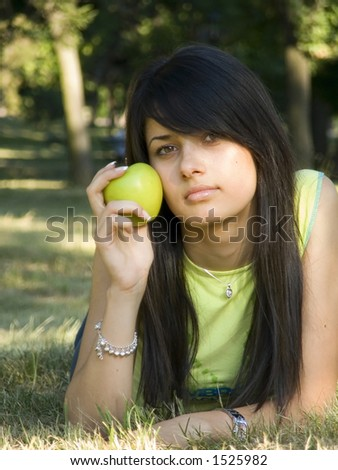 beautiful girl lying on grass with apple in hand