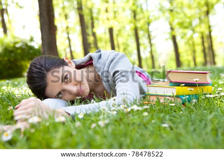 beautiful girl lying on green grass next to books and relaxing - stock photo