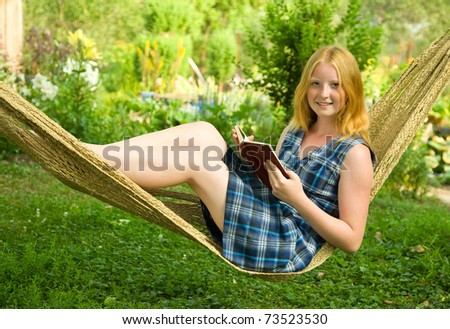 Beautiful girl lying on hammock reading while on vacation