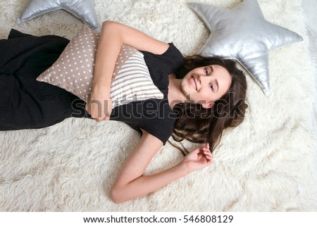 Beautiful girl lying on her back hugging the pillow Enjoy your stay