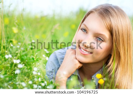 Beautiful Girl lying on Meadow of Flowers and Green Grass.. Happy and Smiling
