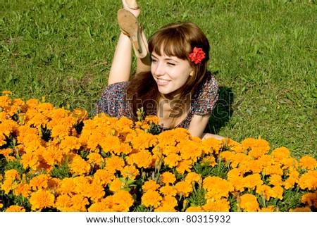 Beautiful girl lying on meadow with flowers - stock photo