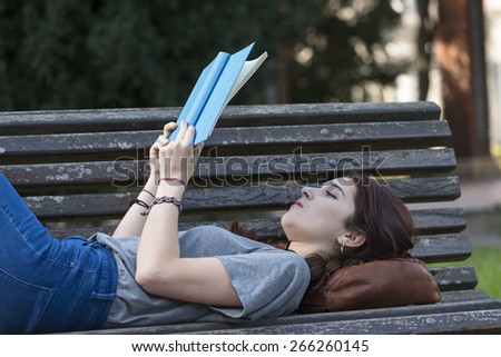 Beautiful girl lying on old wood bench and reading blue book, outdoor. - stock photo