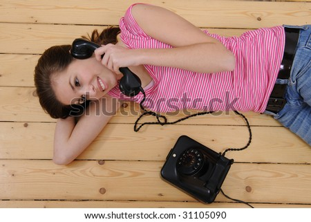 beautiful girl lying on the floor and talking on phone at home - stock photo