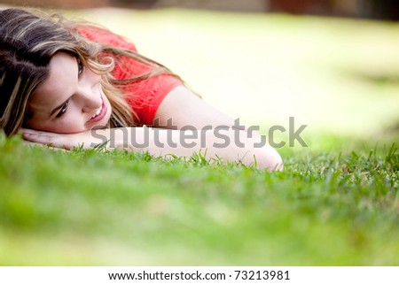 Beautiful girl lying on the floor outdoors and smiling