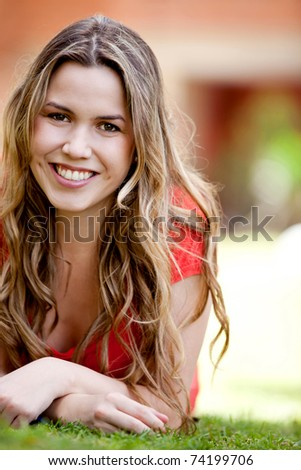 Beautiful girl lying on the floor outdoors and smiling - stock photo