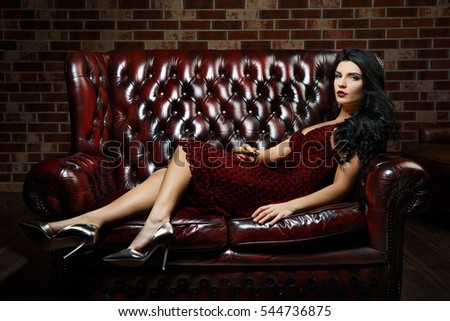 beautiful girl lying on the sofa. red dress. curly black hair