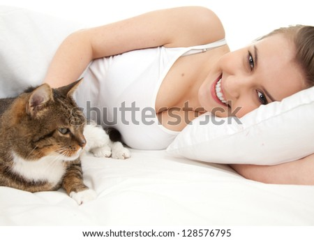 beautiful girl lyng in white bedding with cat, white background