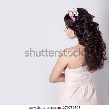 beautiful girl make her hair curls on long black hair decorated with a wreath of flowers - stock photo