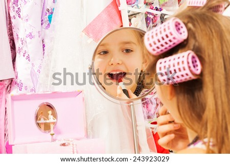 Beautiful girl makes up her face looking in mirror - stock photo