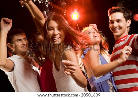 Beautiful girl making gesture meaning to join her dancing friends at party - stock photo