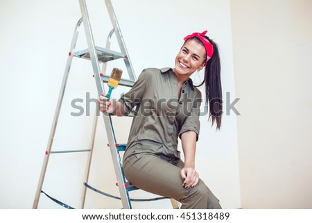 Beautiful girl making repairs on a ladder in the apartment
