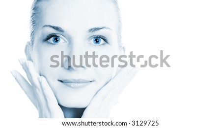 Beautiful girl massages her face toned in blue - stock photo
