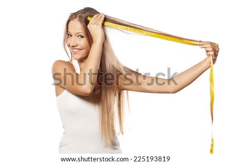 beautiful girl measured her hair with a measuring tape - stock photo