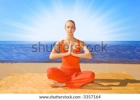 Beautiful girl meditating on the beach - stock photo