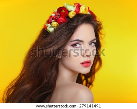Beautiful girl model with flowers in long brown wavy hair isolated on yellow studio background. Makeup. Care. Treatment.