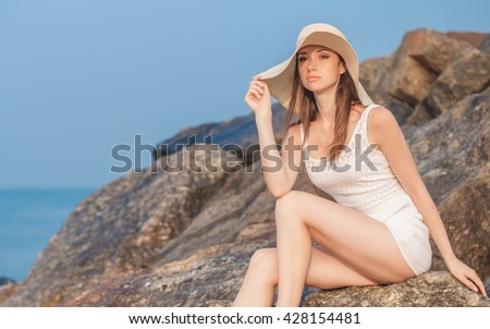 beautiful girl model with hat posing on a rock on the beach. woman rock beach, woman rock beach ocean, woman model beach, woman rock travel, girl model beach, girl model beach relax, girl model sexy - stock photo