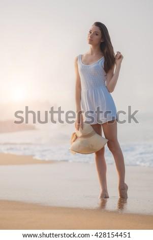 beautiful girl model with hat posing on the beach sunset. woman beach, woman ocean, woman model sea, woman travel, girl model hat, girl model beach posing, girl model sexy, woman water, girl sand - stock photo