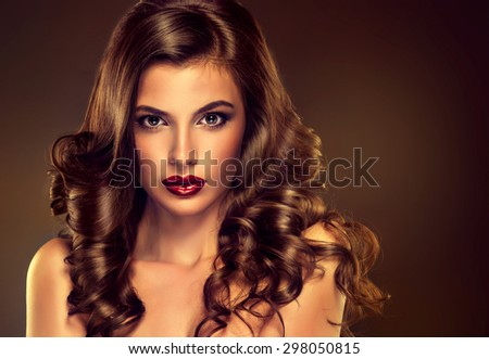 Beautiful girl model with long brown curled hair  and fashion makeup - stock photo