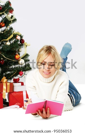 Beautiful girl near christmas tree with gift isolated on white background