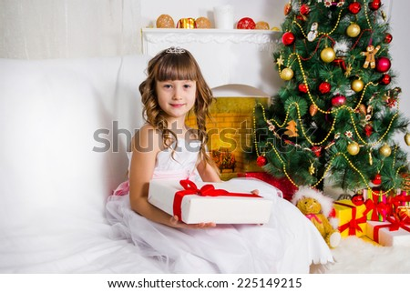 Beautiful girl near the decorated Christmas tree, holds a white gift - stock photo