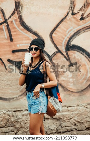 beautiful girl near the graffiti wall - stock photo