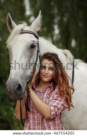 Beautiful girl near the horse. Ginger hair girl in chekered shirt with white horse.