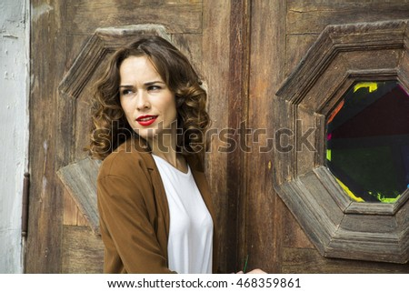 Beautiful girl near the wooden door.