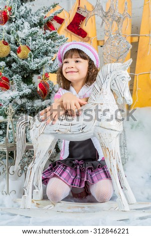 beautiful girl next to a horse rocking near a Christmas tree - stock photo