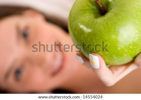 Beautiful girl offering green apple - health and beauty ( focus on apple)