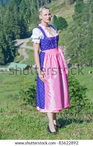 Beautiful girl on a Bavarian alpine meadow in the mountains /Summer in the mountains - stock photo