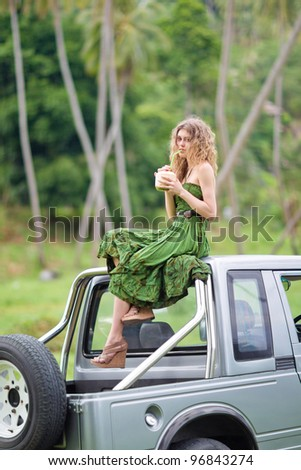 Beautiful girl on a car drinking coconut - stock photo