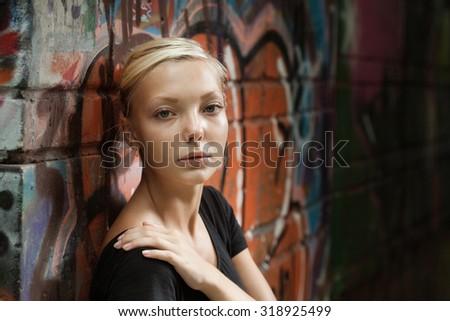 beautiful girl on a city street near a wall of graffiti - stock photo