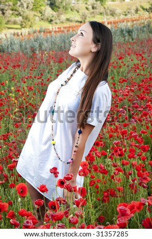 Beautiful girl on a field with poppies - stock photo