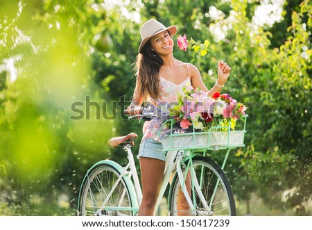 Beautiful Girl on Bike in Countryside Smelling Flowers, Summer Lifestyle  - stock photo