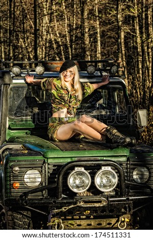 Beautiful girl on camouflage outfit sitting top of the off-road vehicle bonnet - stock photo