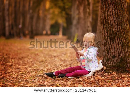 beautiful girl on nature with the tablet
