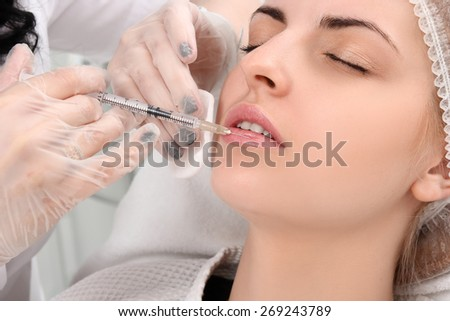 Beautiful girl on rejuvenation procedure in beauty clinic, filler injection. - stock photo
