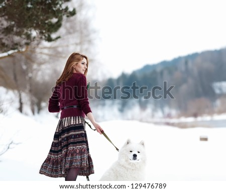 Beautiful girl on the bank of the river with a white dog - stock photo