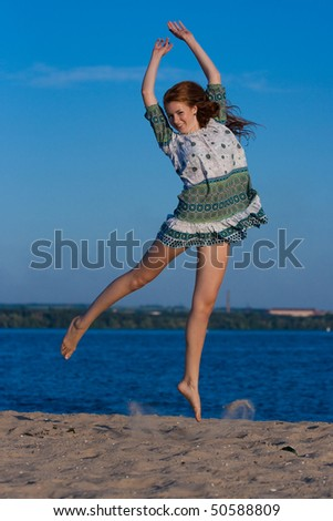 beautiful girl on the beach in summer jumping - stock photo