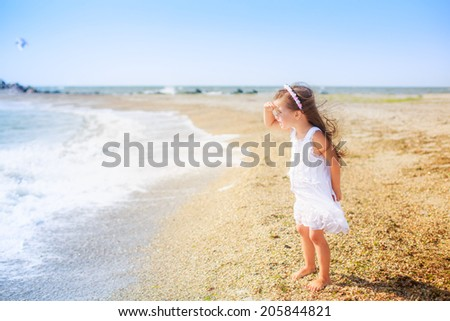 beautiful girl on the beach looking into the distance, wind