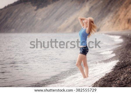 beautiful girl on the beach. the wind inflates hair - stock photo