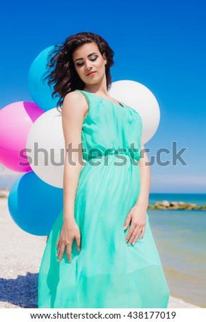 Beautiful girl on the beach with colorful balloons in summer