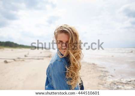 Beautiful Girl on The Beach. Woman enjoys wind. Summertime fun concept. Travel and Vacation. Soft focus.